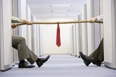 2 businessmen playing Tug of war - Office Politics