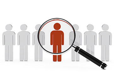 Magnifying glass over icons of people - Headhunting and Recruiting new employees