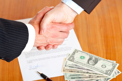 Two hands shaking over a pen and contract - Salary Negotiation