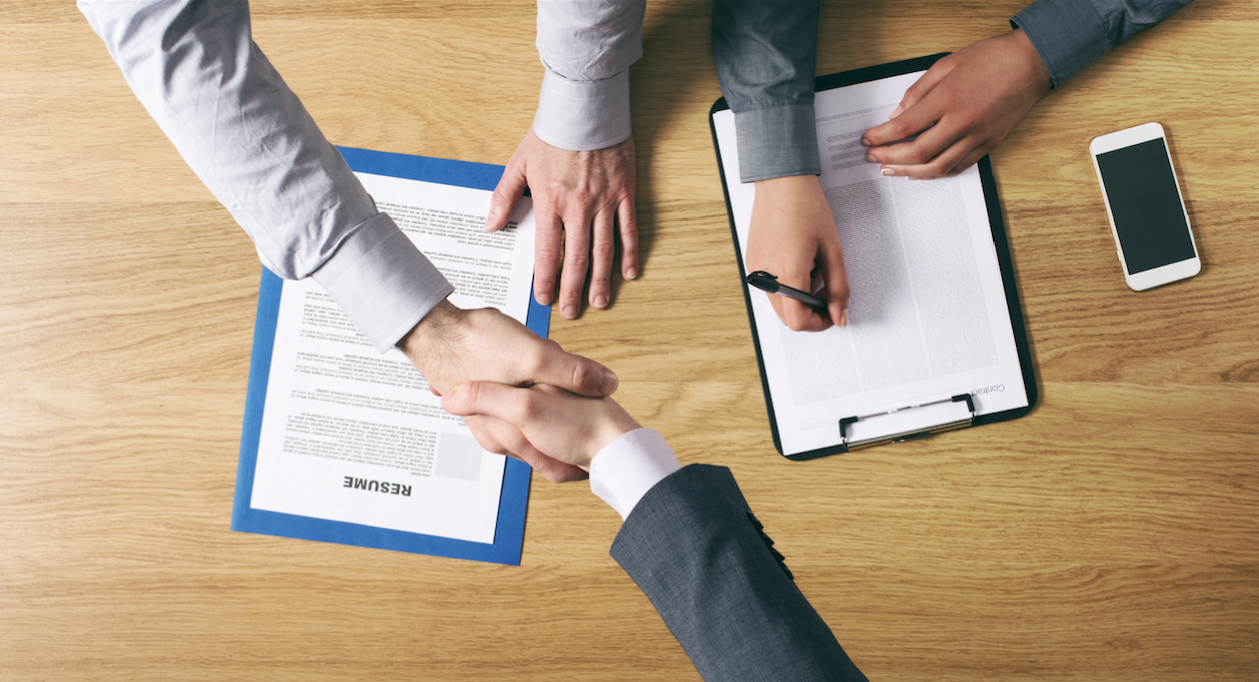 Employer shakes hands with candidate over resume - Interview Tips